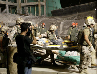 German soldiers rescue an injured worker from a dilapidated building on the construction site of the Jamhoriat Shafakhana, or Republican hospital, in Kabul